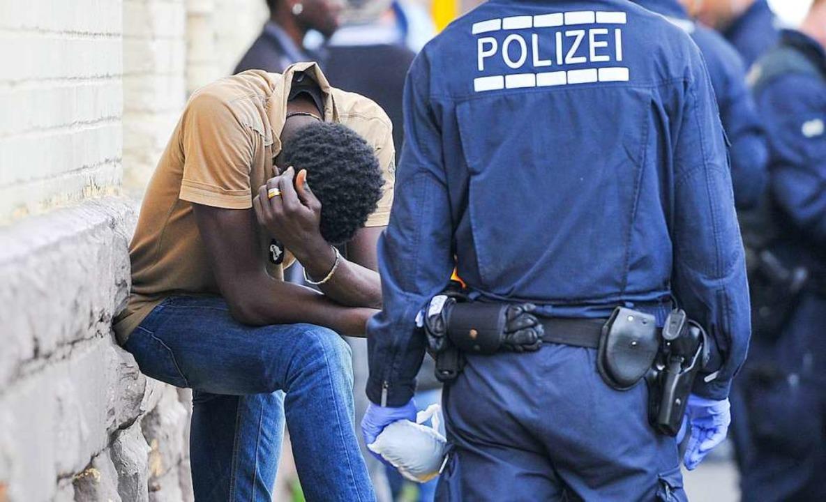 Ein Polizist überwacht bei einer Razzia einen Verdächtigen.  | Foto: dpa