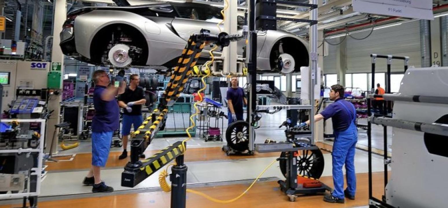 Mit der Umstellung vom Verbrennungs- a...rid-Fahrzeugs BMW i8 im Werk Leipzig.   | Foto: Sebastian Willnow (dpa)