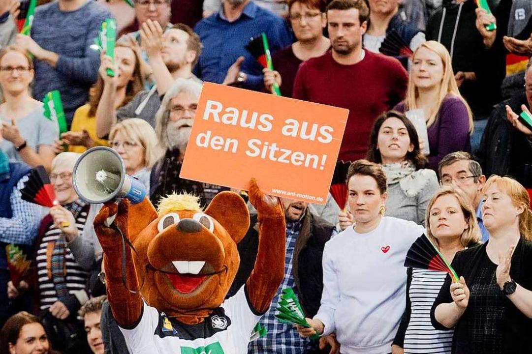 Maskottchen Hanniball animiert das Publikum beim Testspiel gegen Tschechien.  | Foto: dpa