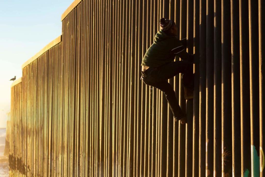 Ein Migrant aus Honduras versucht den ...erikanischen Grenzzaun zu überwinden.     Foto: AFP