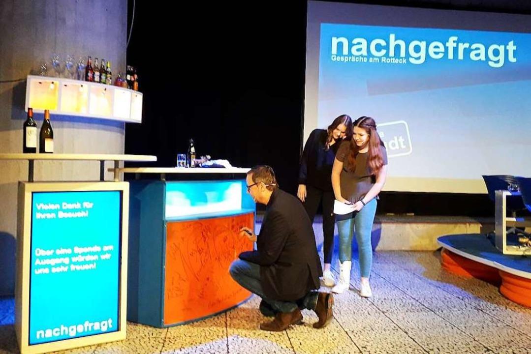 Matthias Brandt unterschreibt wie Dutz...Gäste vor ihm auf der Nachgefragt-Bar.    Foto: Fabian Vögtle