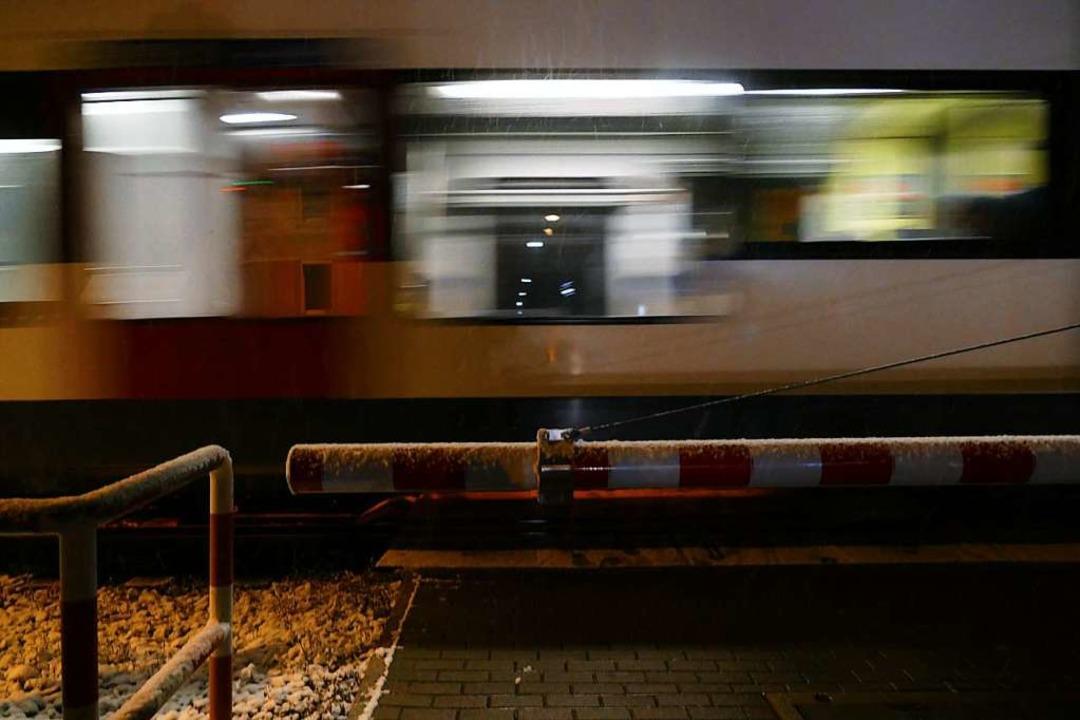 Die Schranke  am kleinen Bahnübergang ...n ist unten, eine S-Bahn fährt vorbei.    Foto: Peter Gerigk