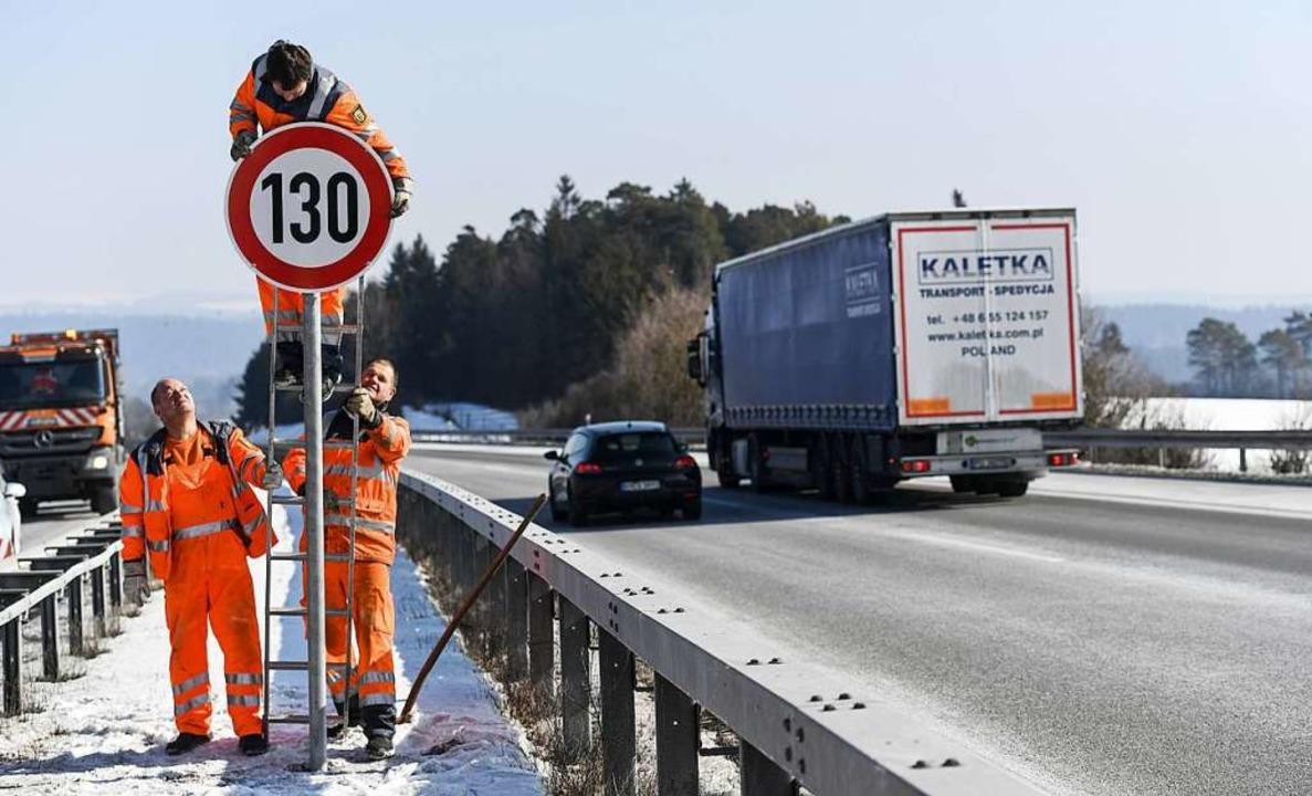 """Straßenwärter montieren an der Autobah...mit der Aufschrift """"130"""".     Foto: dpa"""