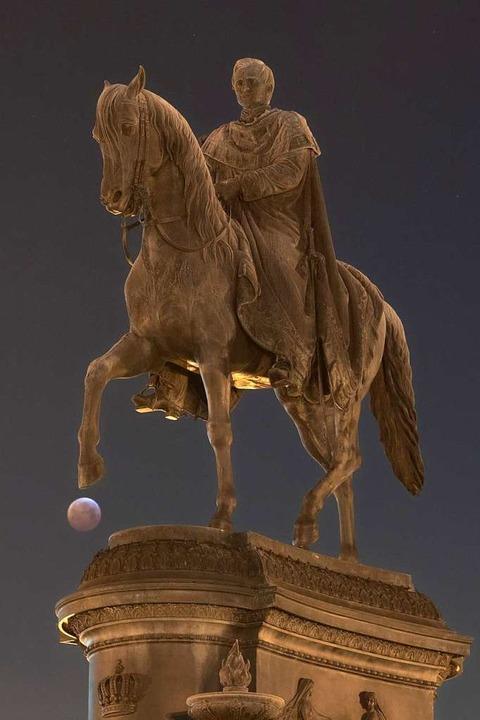 Der Blutmond hinter dem Reiterstandbild des sächsischen Königs Johann in Dresden  | Foto: dpa