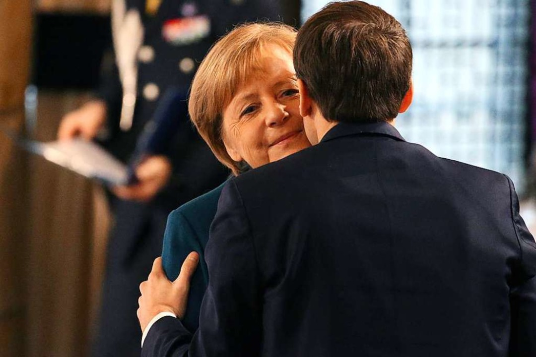 Angela Merkel und Emmanuel Macron begrüßen sich in Aachen.  | Foto: dpa