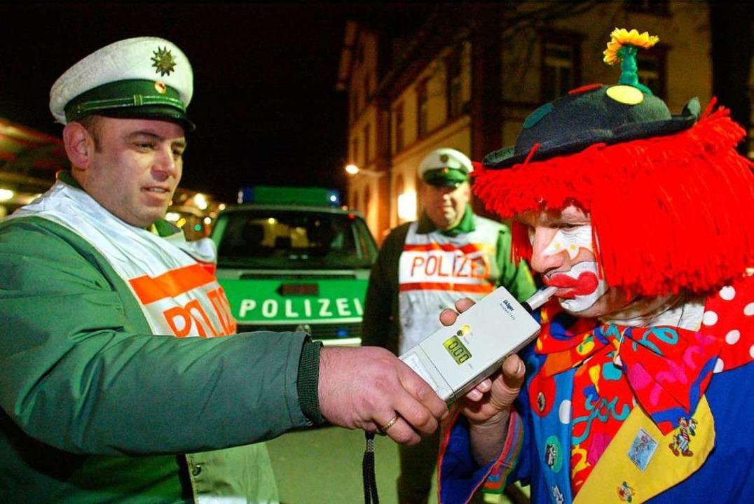 Ein als Clown verkleideter Narr bläst ... in ein Alkoholmessgerät. (Archivbild)    Foto: dpa