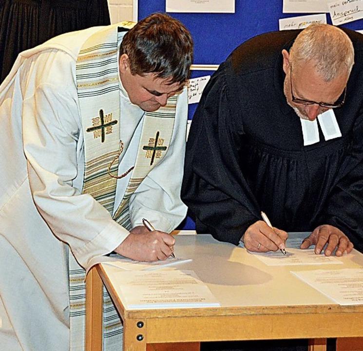 Die Pfarrer  Werner Mühlherr und Fried...nks) unterschreiben die Vereinbarung.     Foto: Gerhard Lück