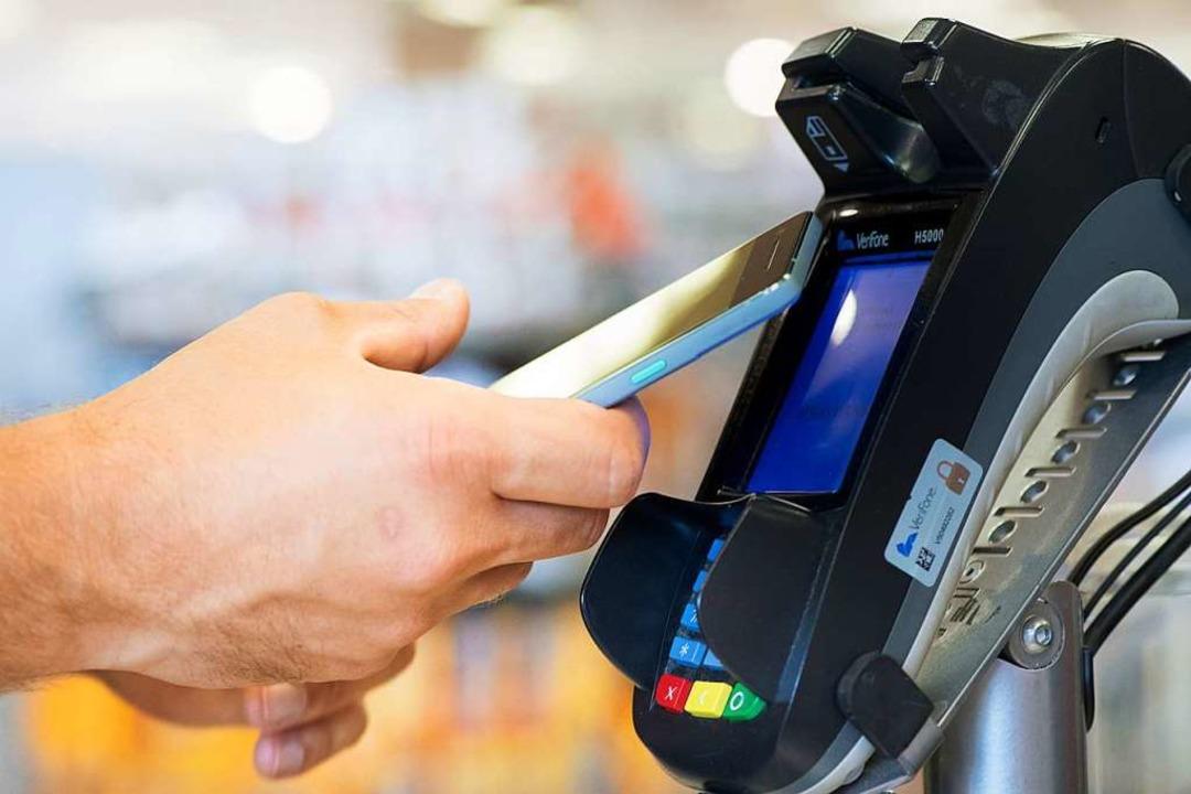 Mobile Payment: Kontaktlose Bezahlen mit dem Smartphone.     Foto: DPA