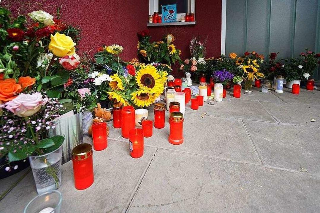 Blumen und Kerzen stehen an der Arztpraxis in Offenburg.  | Foto: dpa