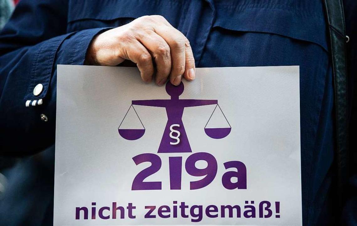 Eine Frau hält bei einer Kundgebung vo...der Aufschrift «219a nicht zeitgemäß!»  | Foto: dpa