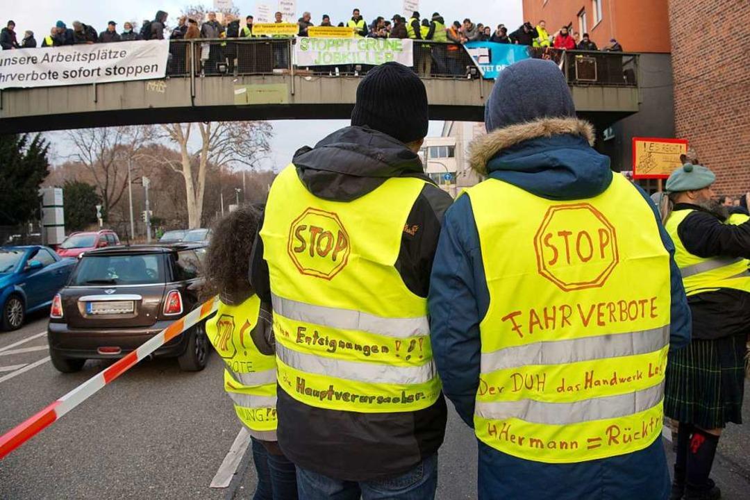 Parolen auf dem Rücken: Demonstranten am Neckartor   | Foto: dpa