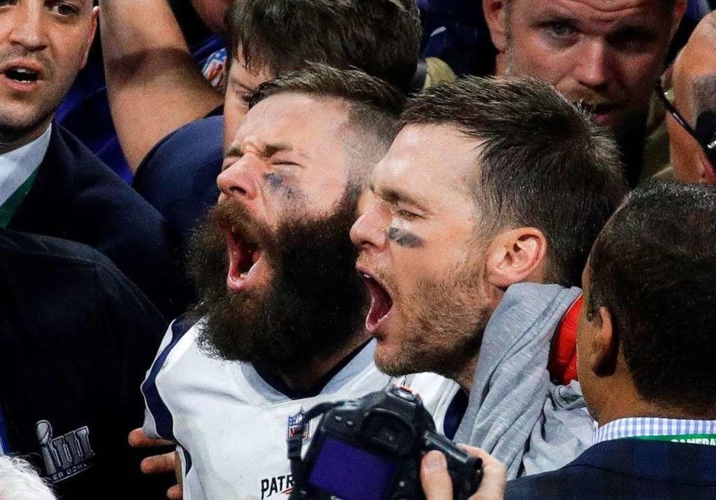 Julian Edelman (M, l) und Tom Brady vo...iots jubeln nach dem gewonnenen Spiel.  | Foto: dpa