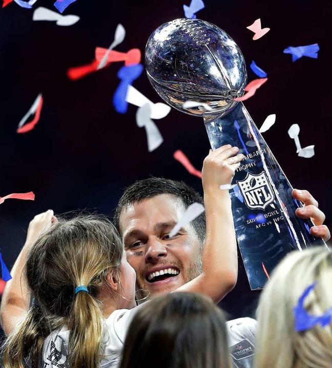 Tom Brady von den Patriots hält nach d...Tocher und die Vince Lombardi Trophäe.  | Foto: dpa