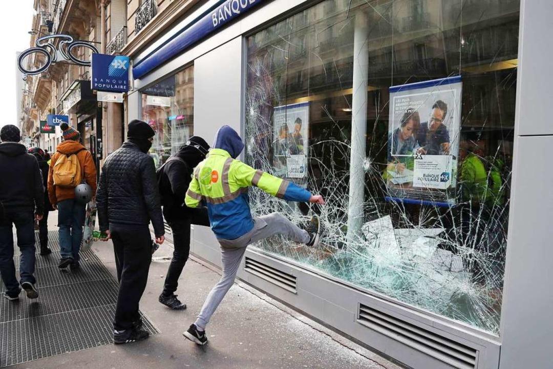 Ein Mann zerstört ein Schaufenster in Paris.    Foto: AFP