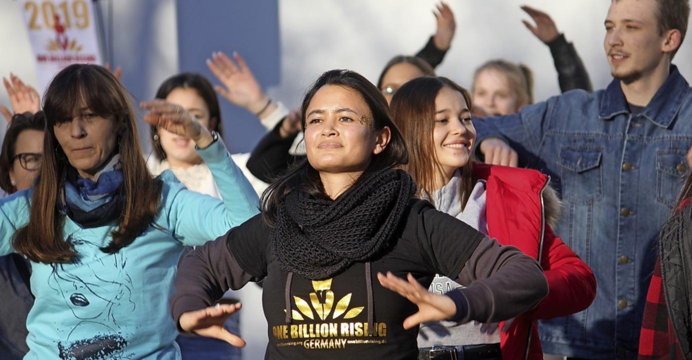Tanzend zeigen die Teilnehmer die rote Karte gegen Gewalt an Frauen.  | Foto: Erik Stahlhacke