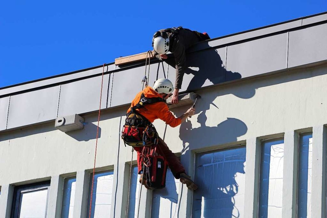 Am Seil hängend und vom Dach aus unter...r Ostfassade der Heiliggeistkirche an.    Foto: Erich Krieger