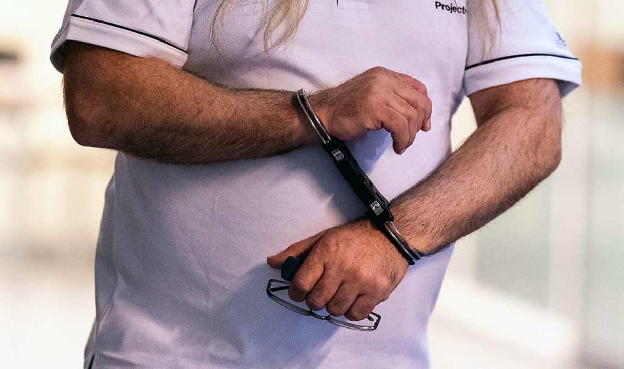 Der Angeklagte wird vor dem Beginn des...al im Freiburger Landgericht gebracht.  | Foto: dpa