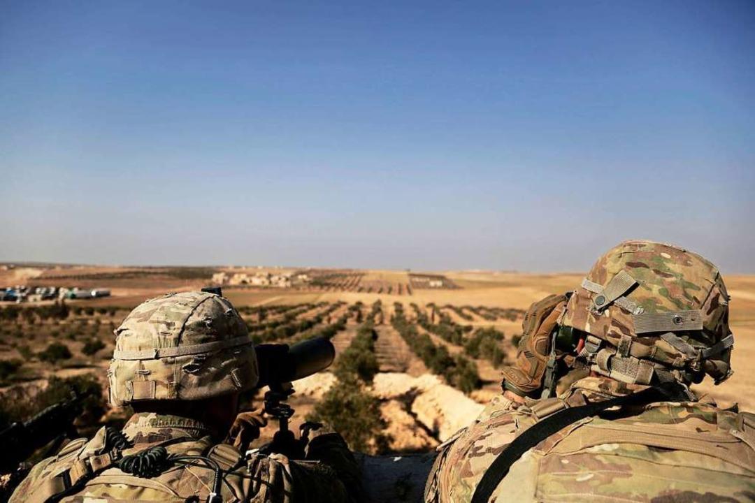 Zwei US-Soldaten schauen von ihrer Bas... Syrien zur türkischen Grenze hinüber.  | Foto: dpa