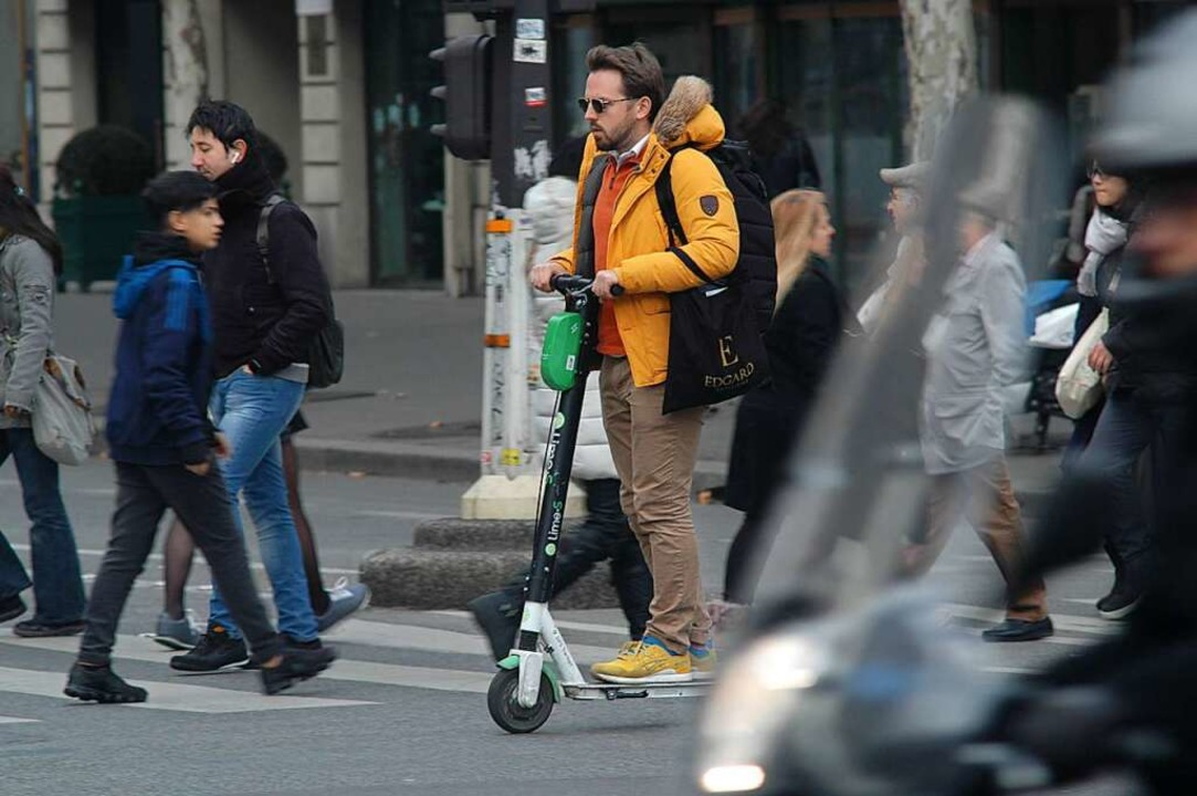 Ein Mann flitzt mit einem E-Tretroller durch Paris.  | Foto: Knut Krohn