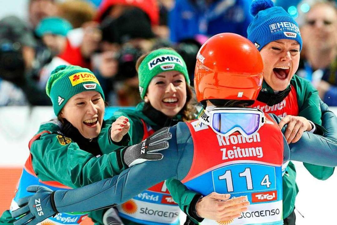 Alle auf eine: Schlussspringerin Katha...ks) erst freudig angelaufen<ppp></ppp>  | Foto: AFP