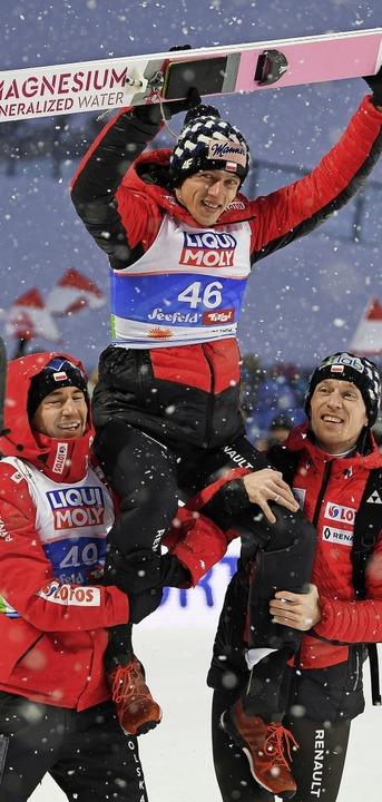 Ein echter Schneekönig: Dawid Kubacki ...und Piotr Zyla getragen und gefeiert.   | Foto: dpa