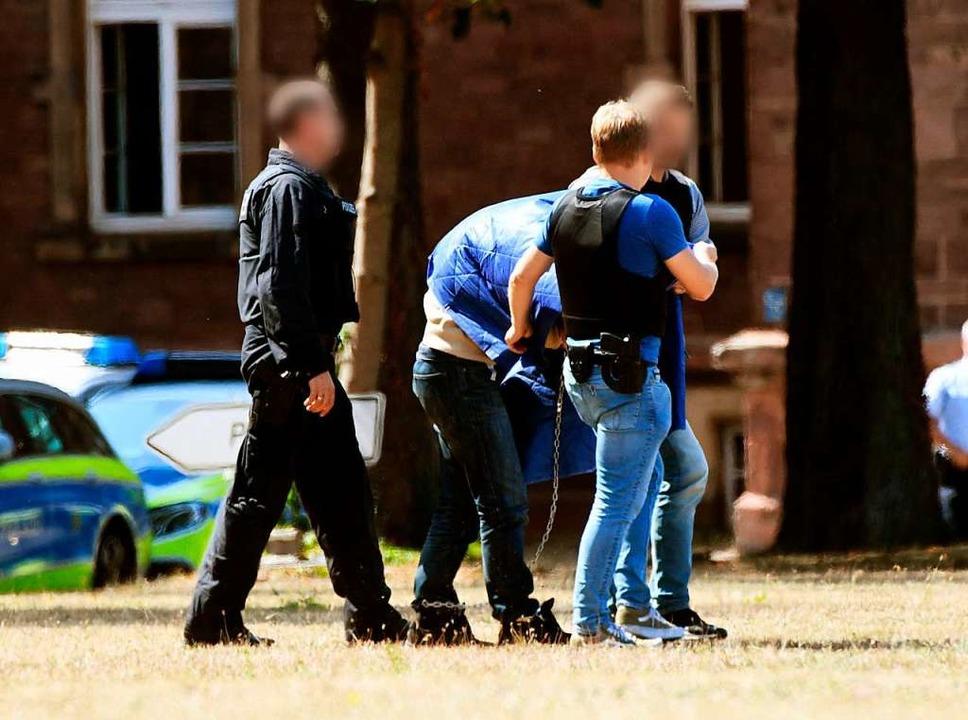 Der Terrorverdächtige Islamist Magomed...beamten zu einem Hubschrauber geführt.  | Foto: Uli Deck
