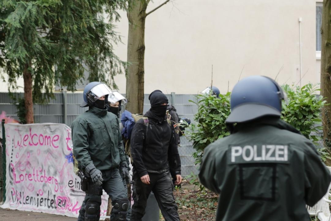 Einer der Besetzer wird aus dem Haus geführt.  | Foto: Jonas Hirt
