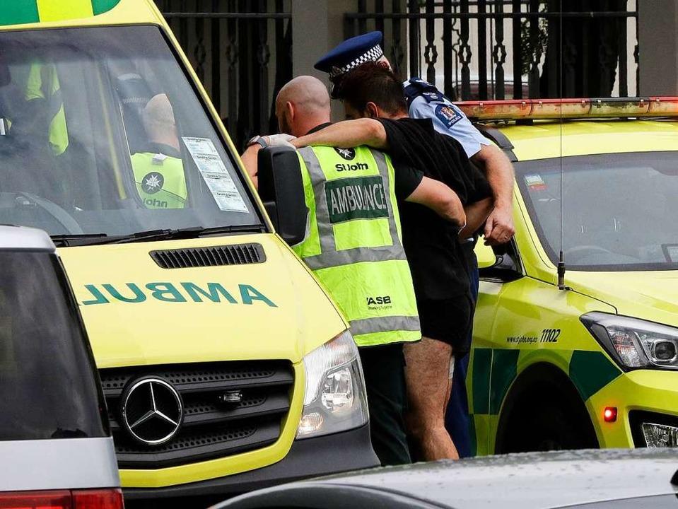 Ein Polizist und Rettungskräfte helfen...m Verwundeten außerhalb einer Moschee.    Foto: dpa