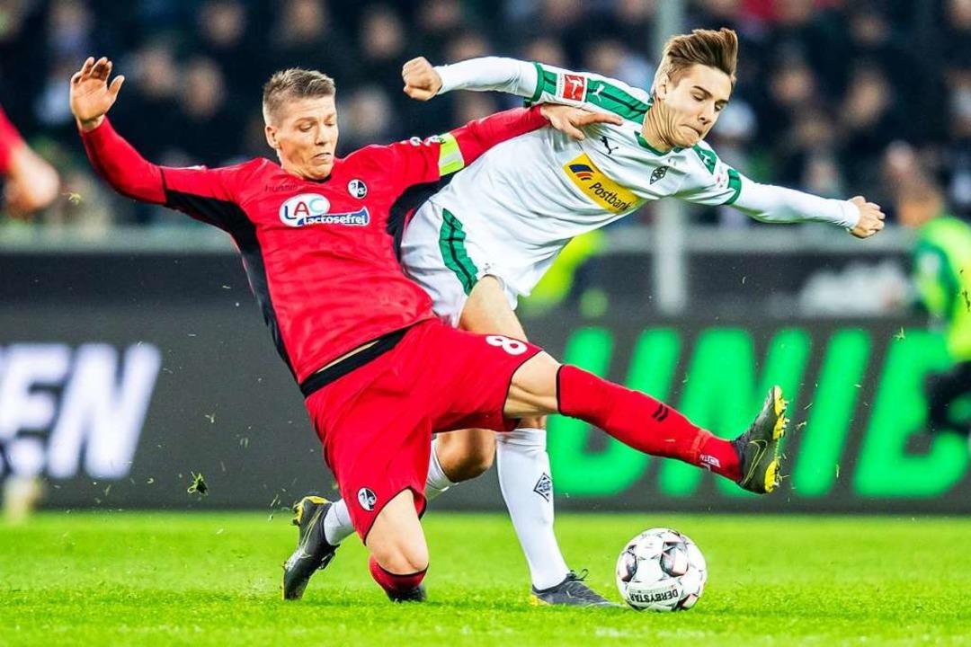Freiburgs Mike Frantz (l) und Gladbachs Florian Neuhaus kämpfen um den Ball.  | Foto: dpa