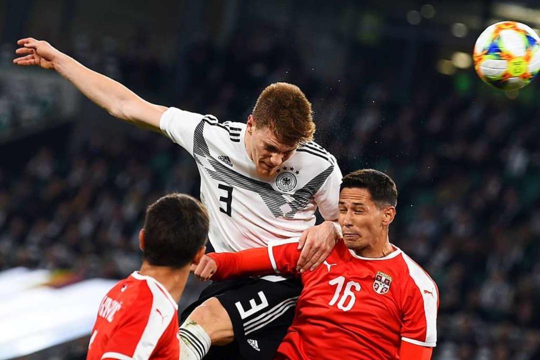 Deutschlands Marcel Halstenberg und Sa... (r.) aus Serbien kämpfen um den Ball.  | Foto: dpa