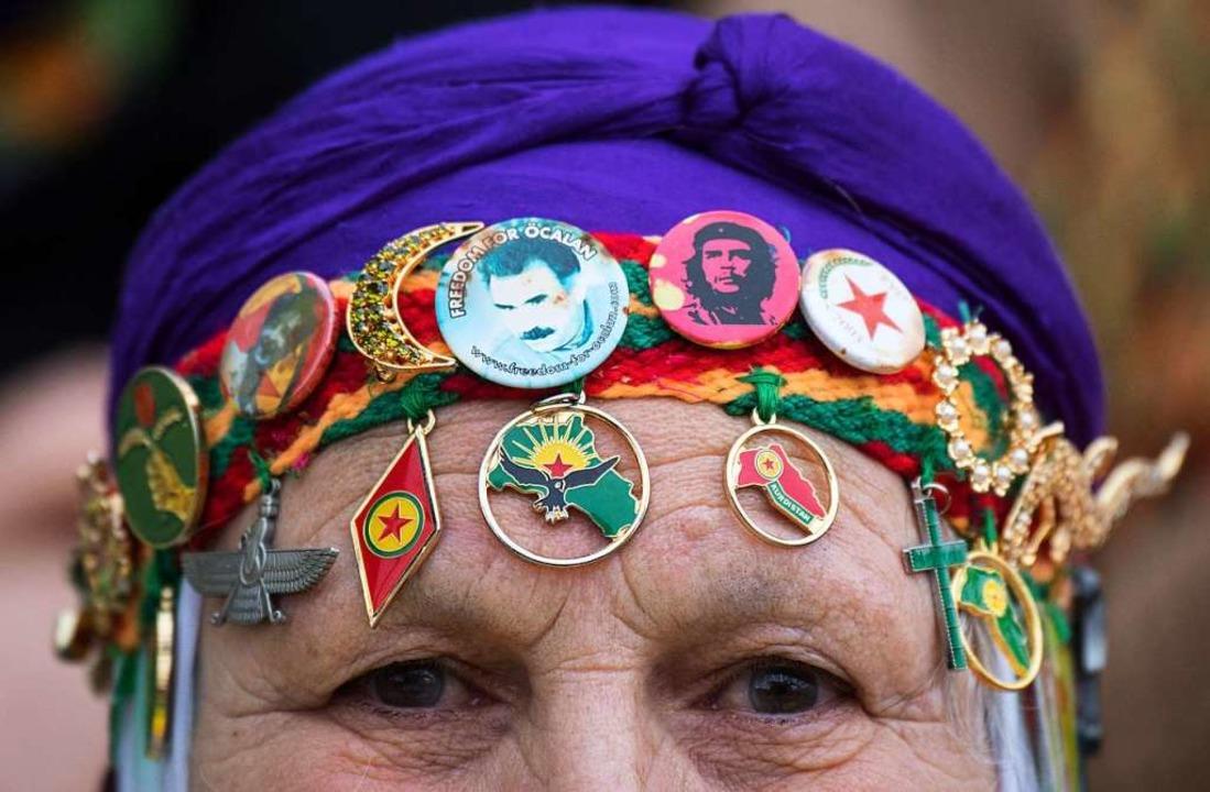 Eine kurdische Demonstrantin geht währ...bdullah Öcalan und von Che Guevara um.    Foto: dpa