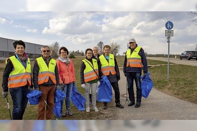 Freiwillige Helfer sammeln Müll von anderen ein