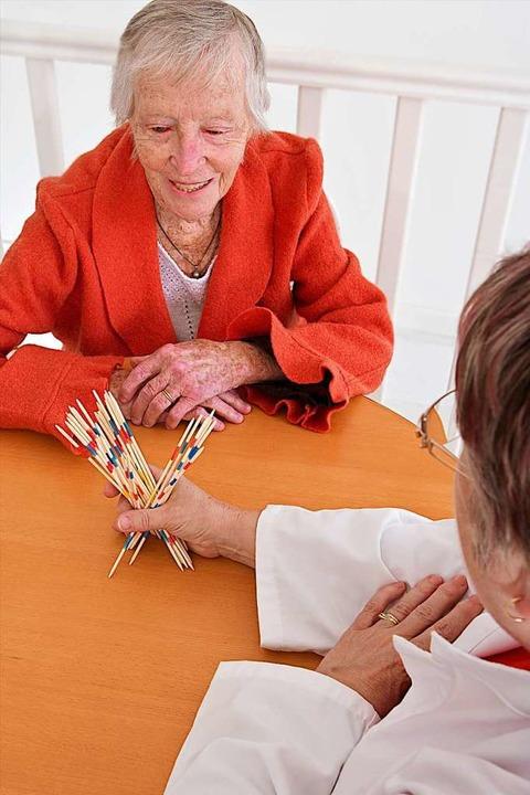 Ein Therapeut macht mit einer Parkinson-Patientin eine Geschicklichkeitsübung.   | Foto: <AUTOR>Jean Paul CHASSENET (stock.adobe.com)</AUTOR>