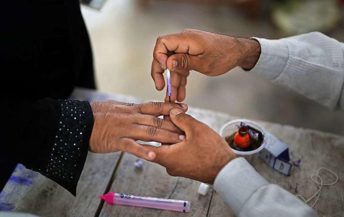 Ein Wahlhelfer färbt in einem Wahlloka... sieben Phasen bis zum 19. Mai statt.   | Foto: dpa