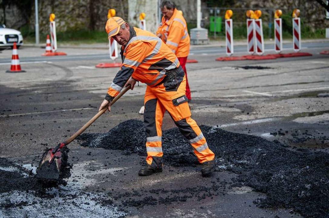Arbeiter schaufeln beim Einbau des Hig...tung durch Stickoxide verringern soll.  | Foto: dpa