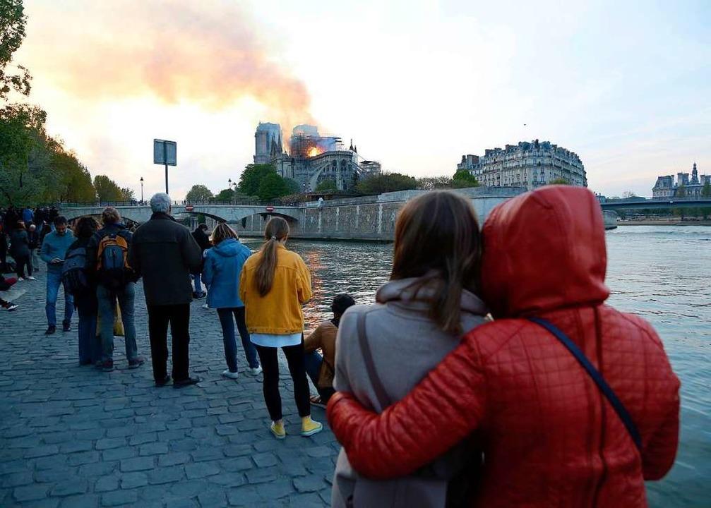 Menschen schauen auf den Brand der Kat...der berühmtesten Wahrzeichen der Welt.  | Foto: dpa