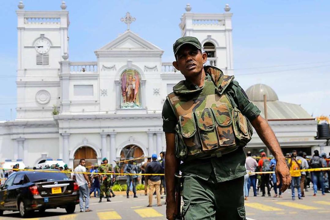 Ein Soldat der sri-lankischen Armee si...hrine nach einer Explosion in Colombo.  | Foto: dpa