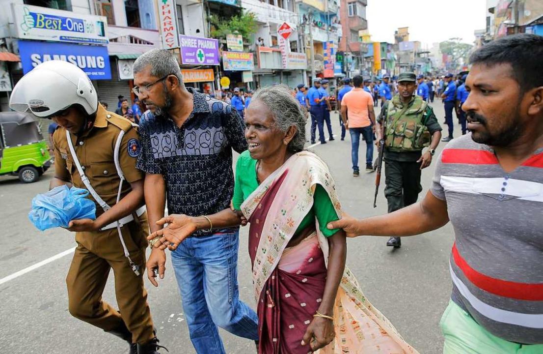 Eine ältere Frau wird in der Nähe des ...o gestützt und in Sicherheit gebracht.  | Foto: dpa