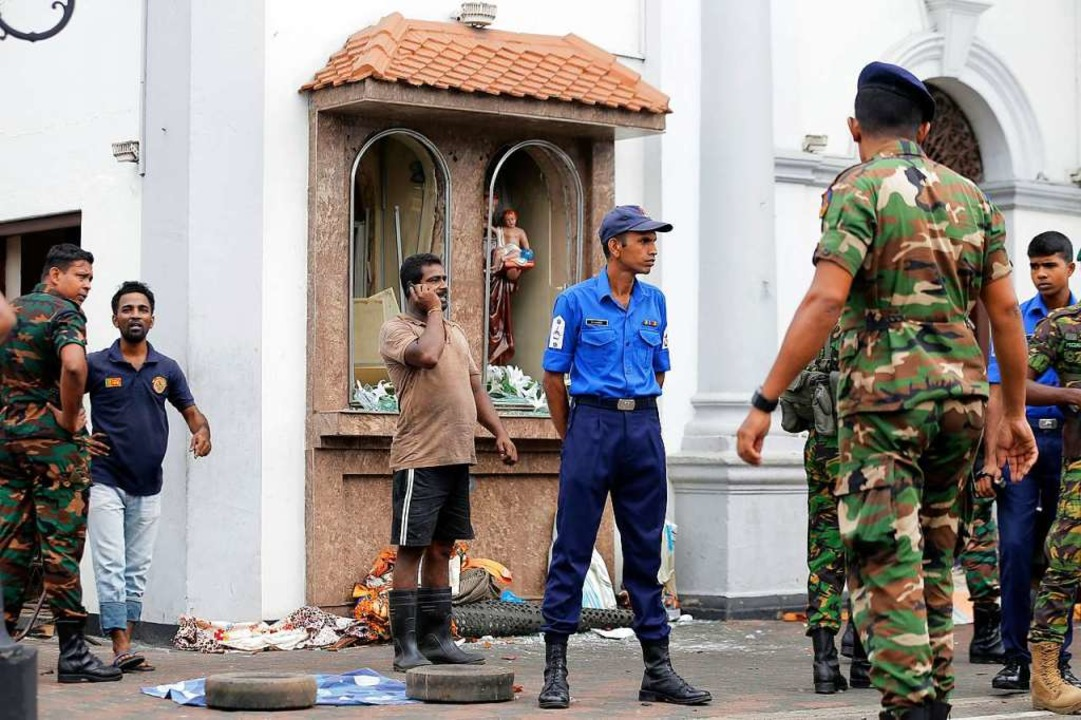 Einsatzkräfte stehen nach einer Explos...m St. Anthony's Shrine in Colombo.  | Foto: dpa