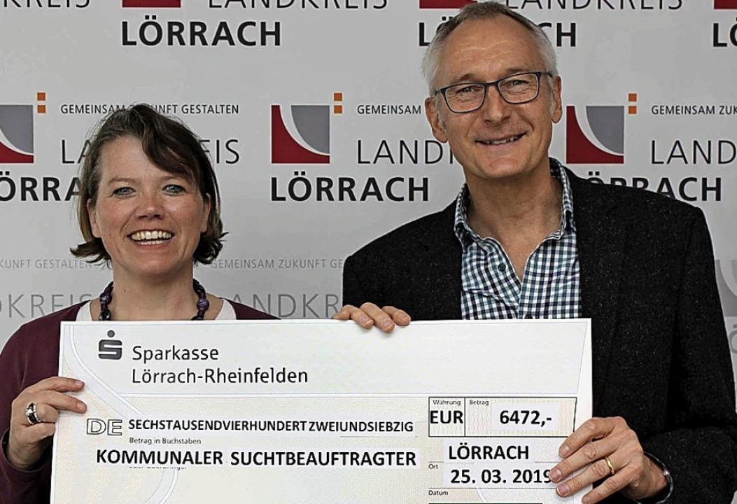 Karin Köhler von der AOK überreicht de...ellmann einen Scheck über 6472 Euro.      Foto: Landratsamt