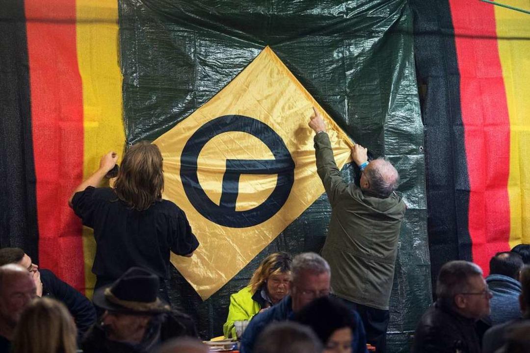 Junge Menschen haben bei rechtsextreme...ngen eine  Fahne der Identitären auf).  | Foto: dpa