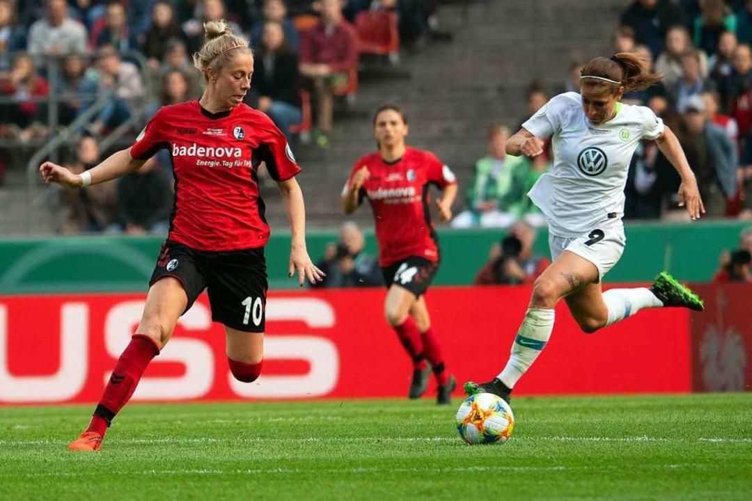Wolfsburgs Anna Blässe  und Freiburgs ... Beck versuchen an den Ball zu kommen.  | Foto: dpa