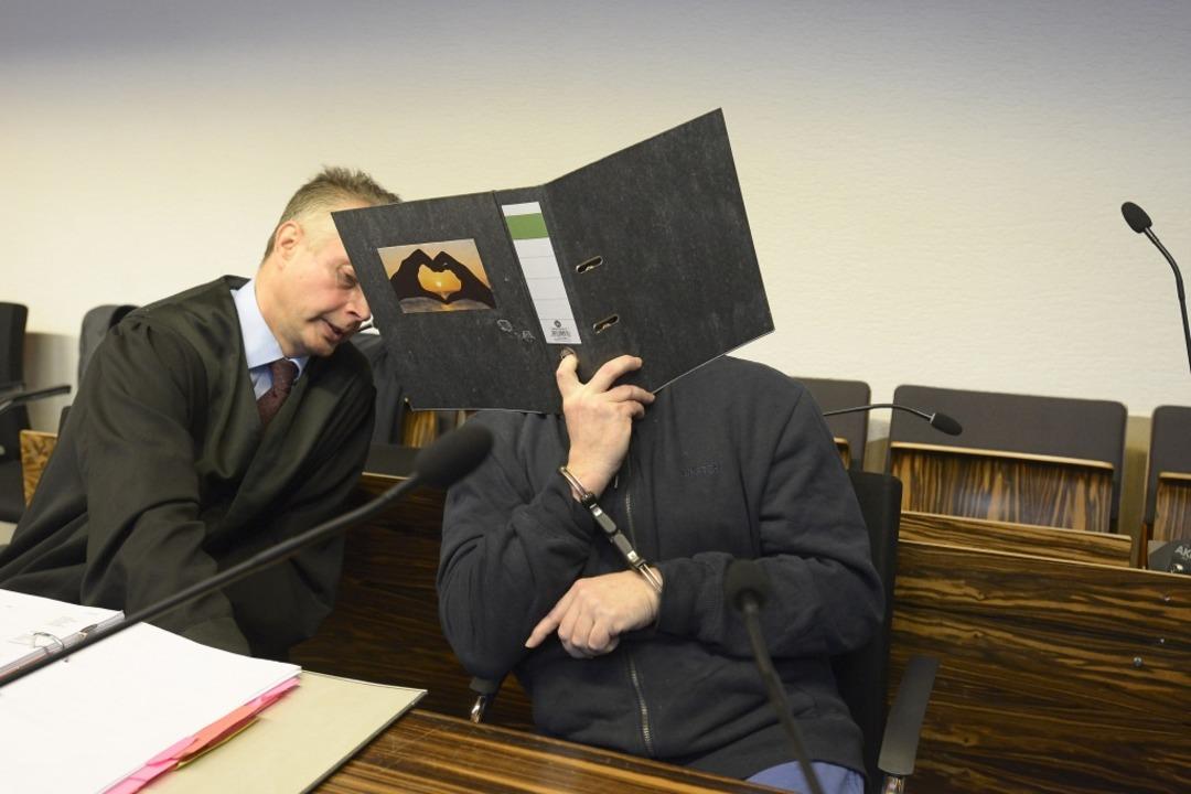 Bernhard H. hält sich einen Aktenordner vor das Gesicht.  | Foto: Ingo Schneider