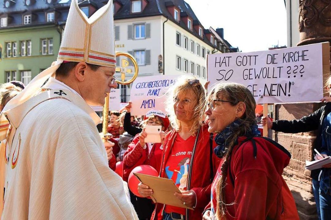 Erzbischof Burger im Gespräch mit zwei...tholikinnen vor dem Freiburger Münster  | Foto: Rita Eggstein