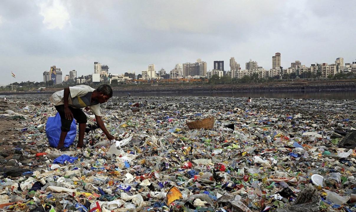 Ein Mann sammelt in Indien Plastikmüll am Strand.  | Foto: Rafiq Maqbool (dpa)