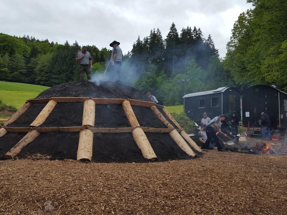 Heiße Glut wird in das Luftloch auf dem Kohlemeiler gegeben.  | Foto: Beate Zehnle-Lehmann