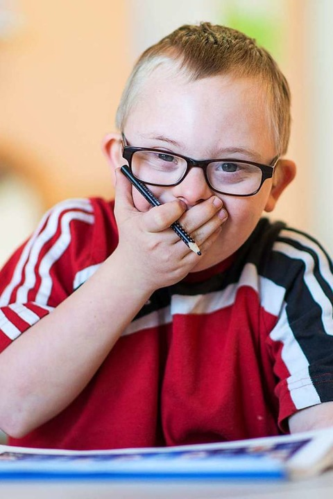 Henri, ein Kind mit Down-Syndrom, sitz...r Schillerschule in einem Klassenraum.  | Foto: dpa