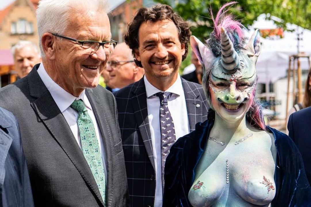Winfried Kretschmann steht neben Cynthia Schneider im Einhornkostüm.    Foto: dpa