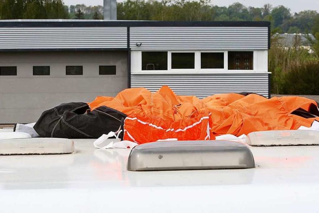 Der Fallschirm eines der Verunglückten...obiles auf dem Parkplatz am Flugplatz.  | Foto: Thomas Warnack (dpa)