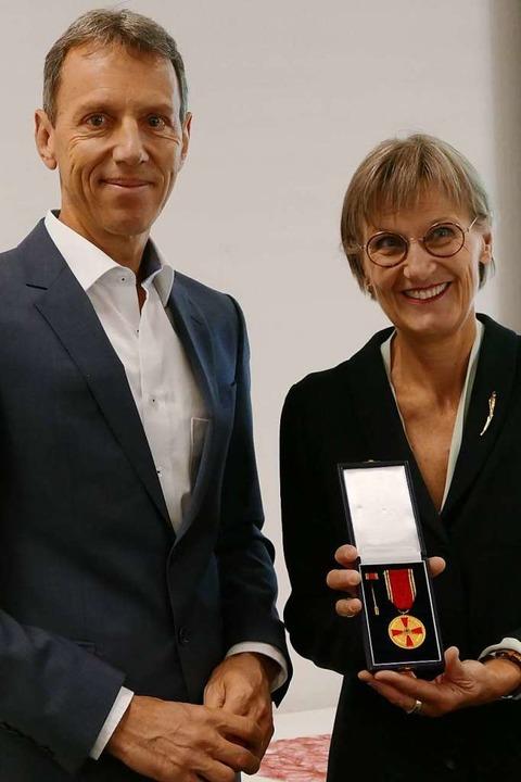 Die Landrätin zeigt das Bundesverdienstkreuz für Klaus-Günther Wiesler.  | Foto: Peter Stellmach